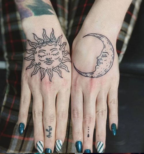 luna y sol tatuaje en mano