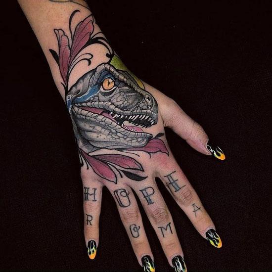 tatuaje velociraptor en la mano