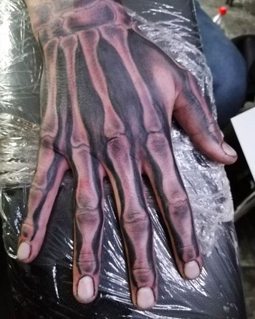 mano tatuada con huesos