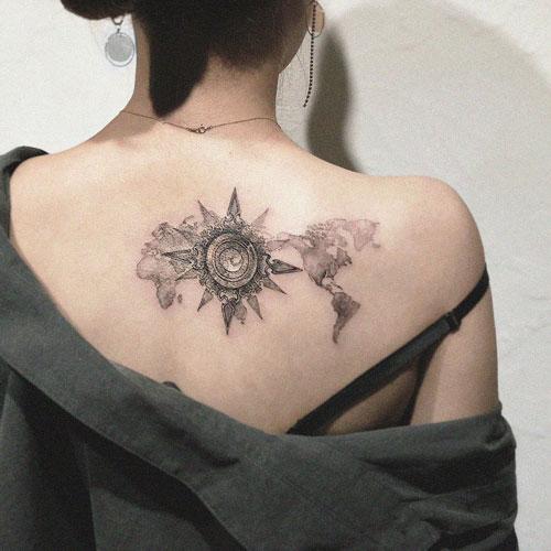 tatuaje mapa y brujula en espalda