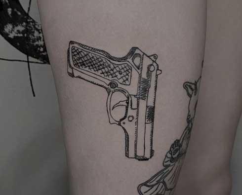 tattoo en piernas de una pistola