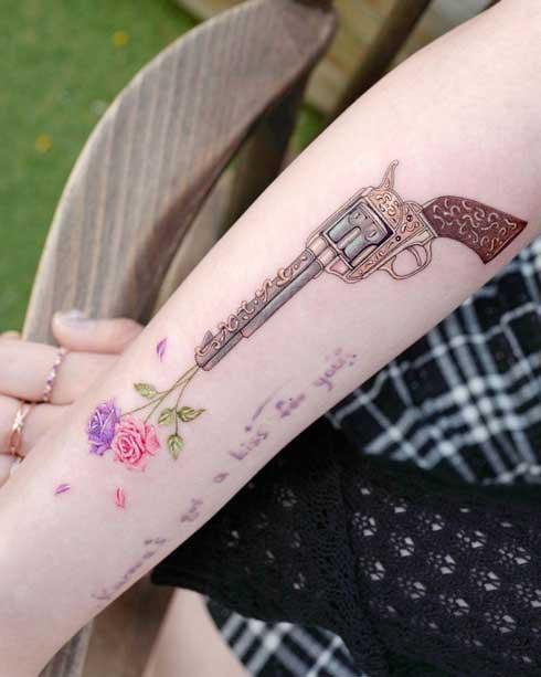 tatuaje de flores y revolver