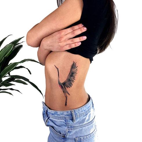 tatuaje grulla en costillas