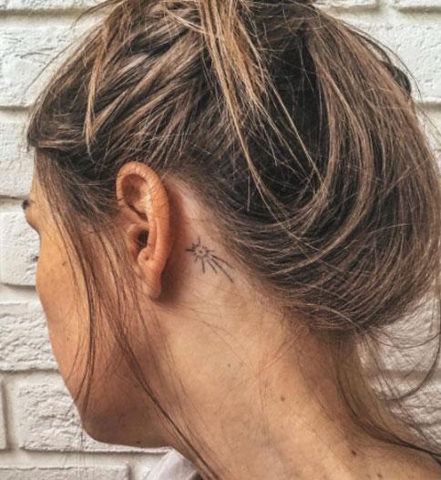tatuaje cometa detras de oreja
