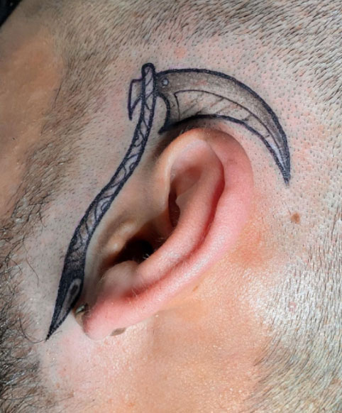 tatuaje de guadaña en rostro