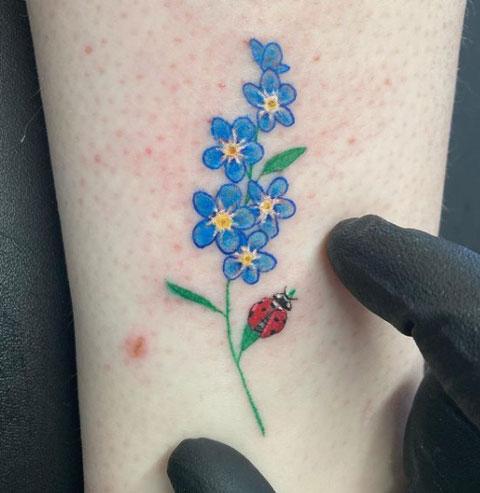 tatuaje mariquita y flores