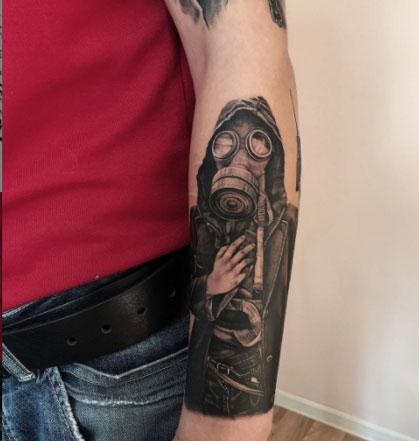tatuaje mascara de gas en brazo